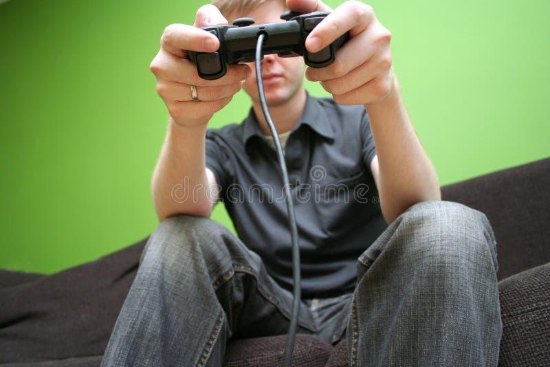 Hombre en el sofá que juega a los juegos video imágenes de archivo libres de regalías