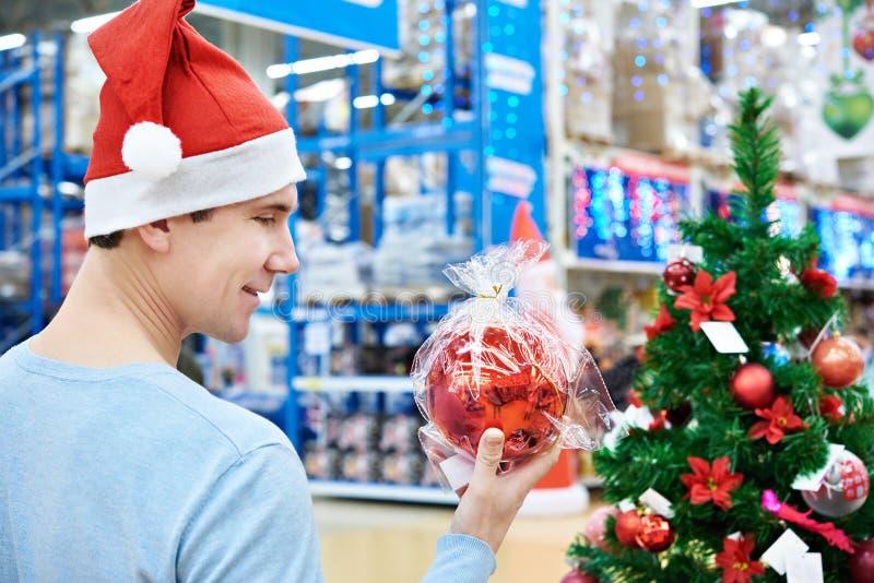 Hombre en el sombrero de Papá Noel que sostiene el árbol de navidad rojo de la bola imagen de archivo libre de regalías