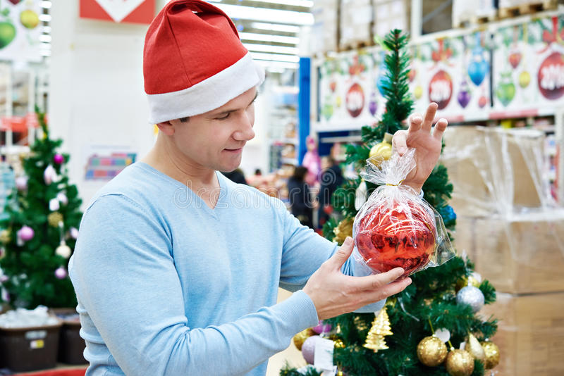 Hombre en el sombrero de Papá Noel que sostiene el árbol de navidad rojo de la bola fotografía de archivo libre de regalías