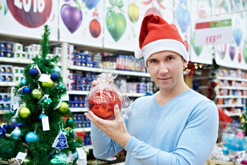 Hombre en el sombrero de Papá Noel que sostiene un árbol de navidad rojo de la bola imagen de archivo