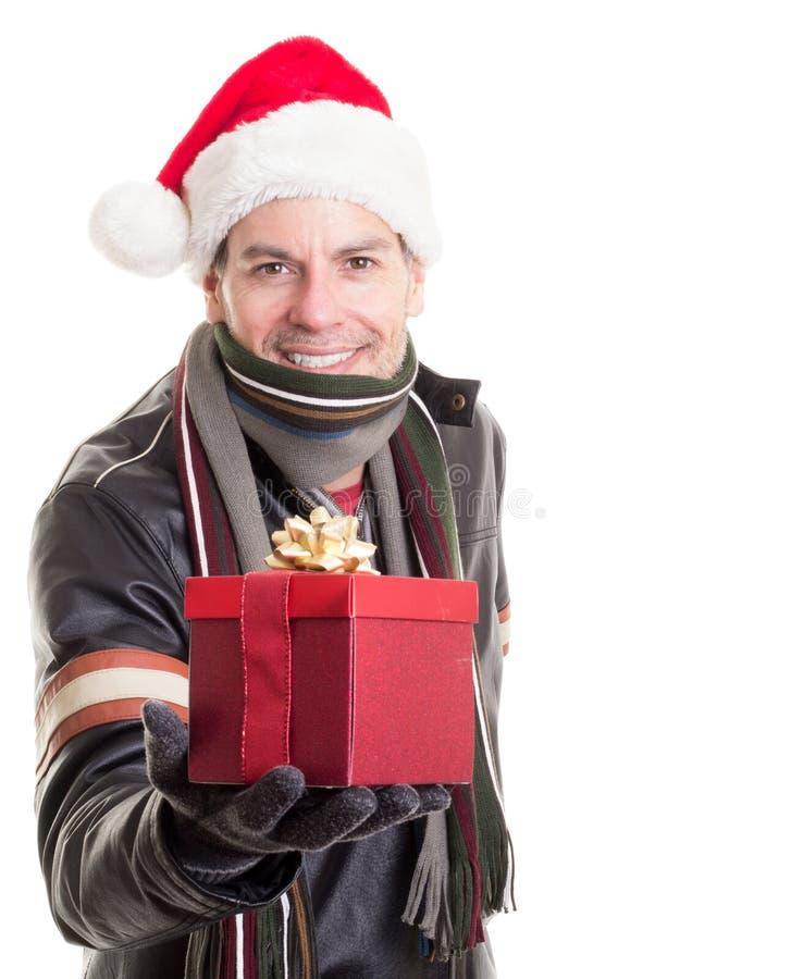 Hombre en el sombrero de Santa con el regalo de la Navidad imagen de archivo