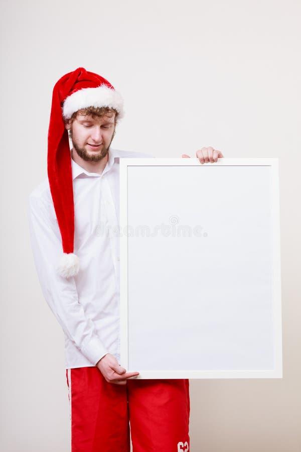 Hombre en el sombrero de santa con la bandera en blanco Copie el espacio imagen de archivo libre de regalías