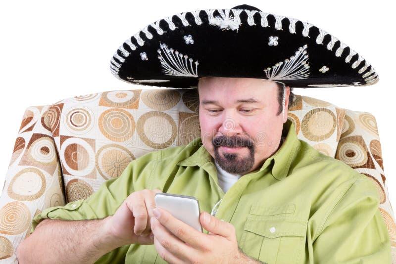 Hombre en el sombrero que manda un SMS en móvil imágenes de archivo libres de regalías