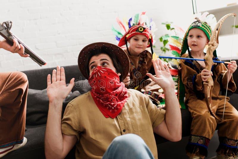 hombre en el sombrero y el pañuelo rojo que juegan así como hijos en trajes indígenas fotos de archivo libres de regalías