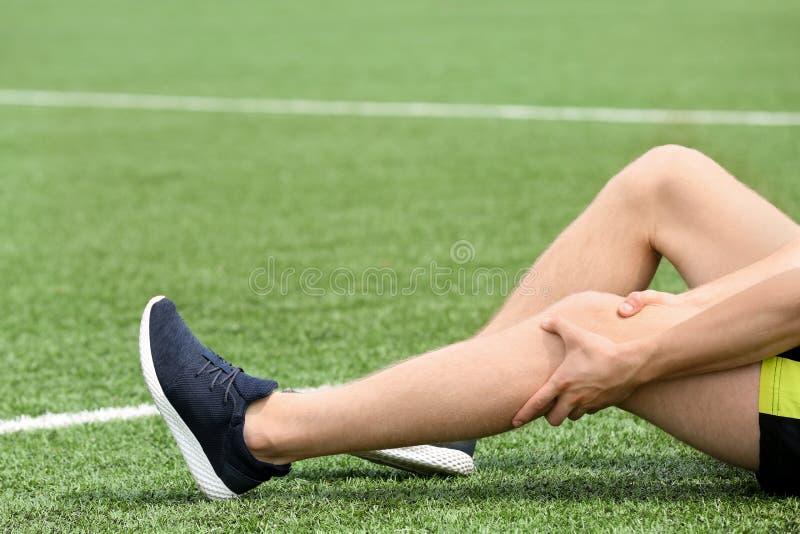 Hombre en el sufrimiento de la ropa de deportes del dolor de la rodilla en el campo de fútbol fotografía de archivo libre de regalías