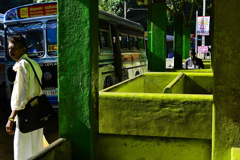 Hombre en el término de autobuses con las paredes verdes claras imagen de archivo
