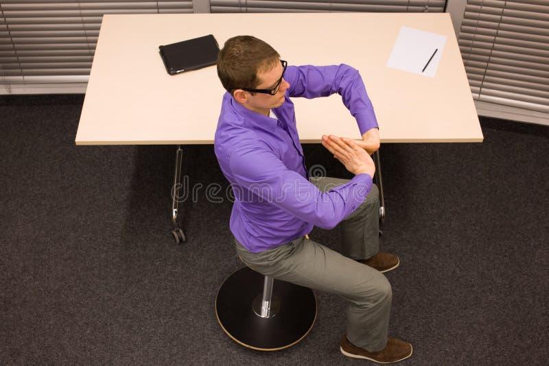 Hombre en el taburete neumático que tiene rotura para el ejercicio en trabajo de oficina foto de archivo libre de regalías