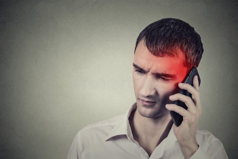 Hombre en el teléfono con dolor de cabeza Concepto móvil celular de la radiación imagenes de archivo