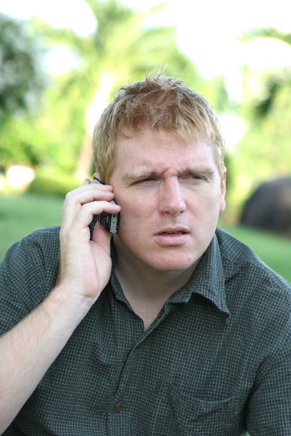 Hombre en el teléfono con una expresión enojada o confusa fotos de archivo libres de regalías