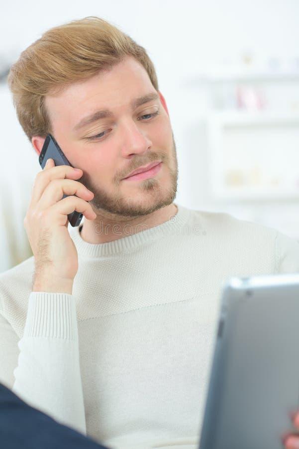 Hombre en el teléfono móvil y la tableta imágenes de archivo libres de regalías