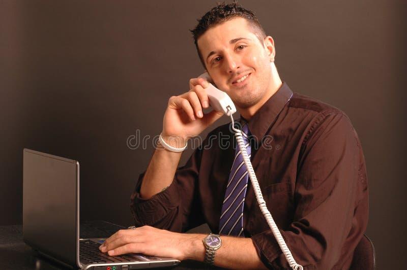 Hombre en el teléfono mientras que en el ordenador 2431 fotografía de archivo