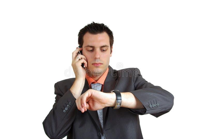 Hombre en el teléfono que mira el reloj foto de archivo
