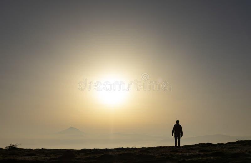 Hombre en el top de la colina que mira paisaje maravilloso de la salida del sol colorida en montañas imagen de archivo libre de regalías