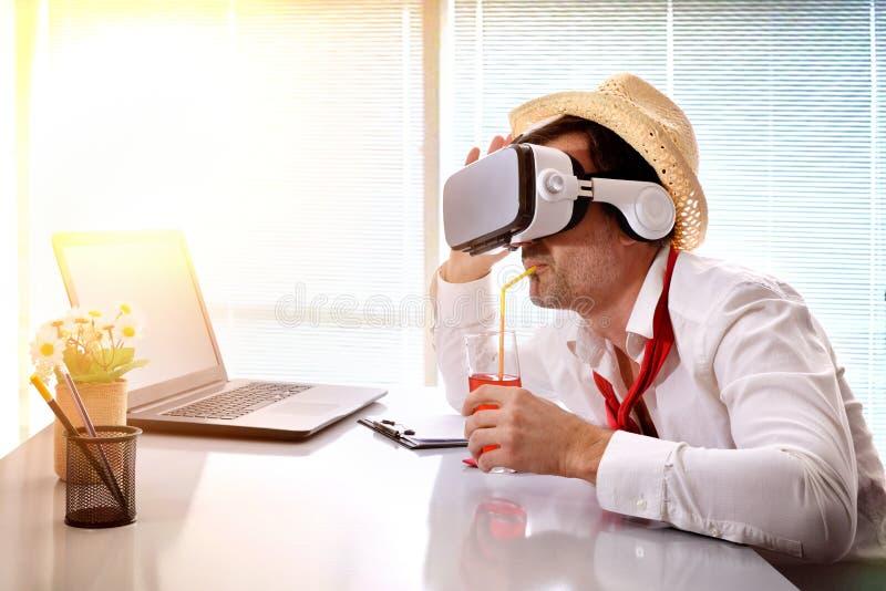 Hombre en el trabajo que se imagina sus vacaciones con la consumición de los vidrios del vr imagenes de archivo