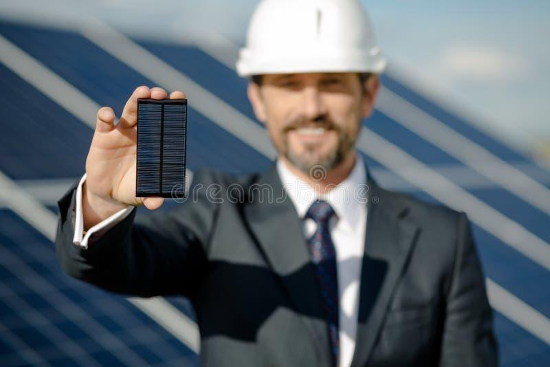 Hombre en el traje de negocios que lleva a cabo el detalle fotovoltaico del panel solar imagenes de archivo
