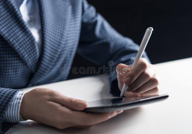 Hombre en el traje de negocios que se sienta en el escritorio con la tableta fotografía de archivo