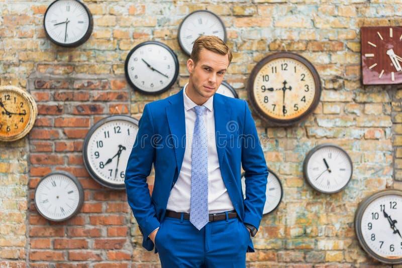 Hombre en el traje que coloca la pared cercana con los relojes fotografía de archivo libre de regalías