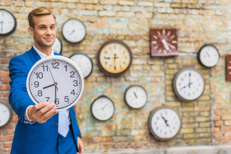 Hombre en el traje que coloca la pared cercana con los relojes imagen de archivo libre de regalías