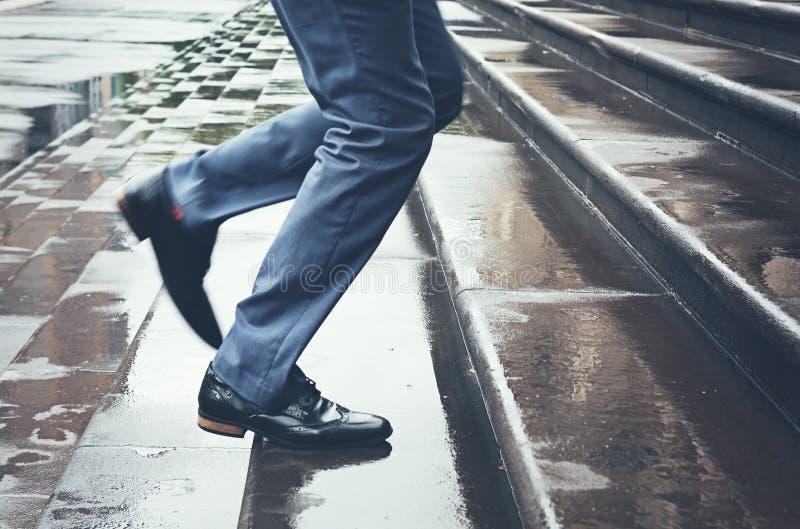 Hombre en el traje que corre tarde encima de pasos en lluvia imágenes de archivo libres de regalías