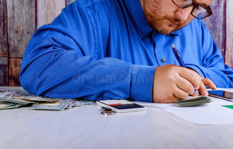 Hombre en el traje que cuenta el negocio que cuenta el dinero americano del billete de banco de los dólares de EE. UU. para la in imagen de archivo