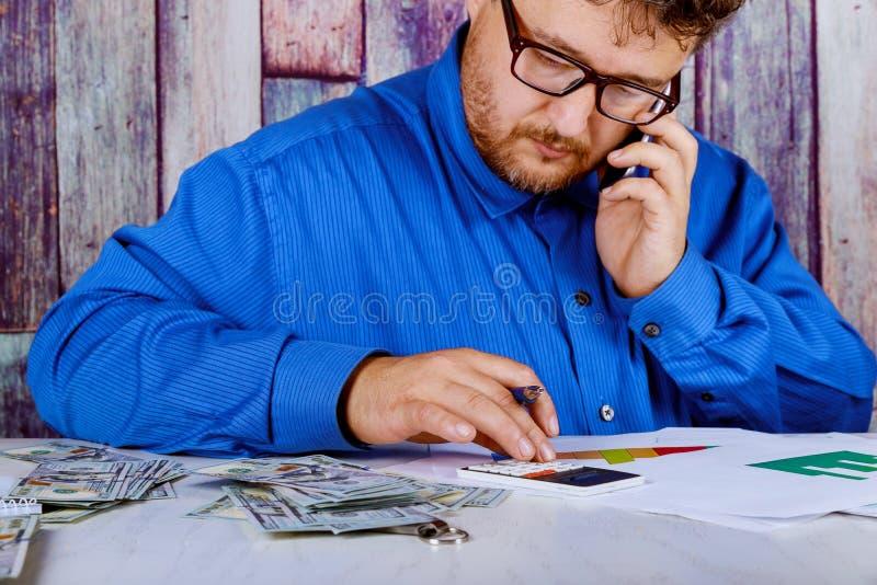 Hombre en el traje que cuenta el negocio que cuenta el dinero americano del billete de banco de los dólares de EE. UU. para la in imagenes de archivo