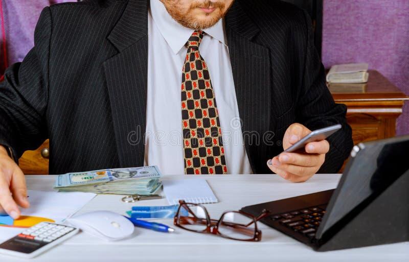 Hombre en el traje que cuenta el negocio que cuenta el dinero americano del billete de banco de los dólares de EE. UU. para la in fotografía de archivo libre de regalías
