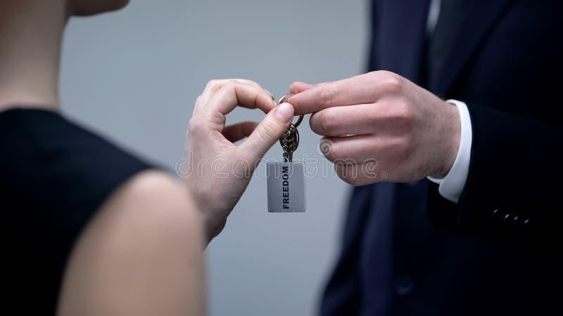 Hombre en el traje que da las llaves a la libertad, cursos de la dirección, autodesarrollo de la mujer fotos de archivo