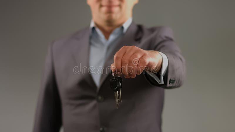 Hombre en el traje que lleva a cabo llaves, alquilando el coche o el apartamento, profesi?n del agente inmobiliario fotos de archivo
