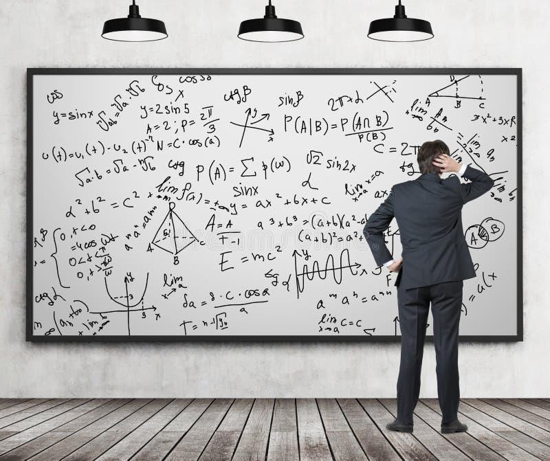 Hombre en el traje que mira whiteboard con fórmulas fotografía de archivo