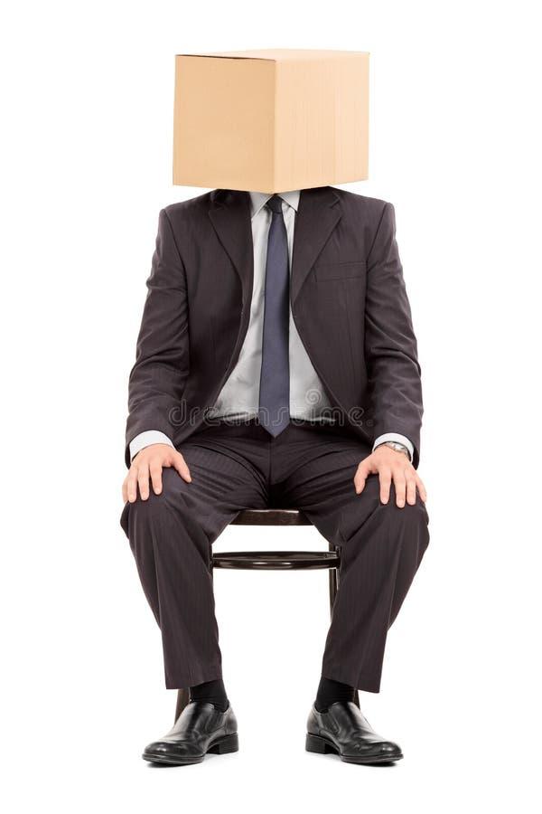 Hombre en el traje que se sienta en una silla con una caja de cartón en su cabeza imagenes de archivo