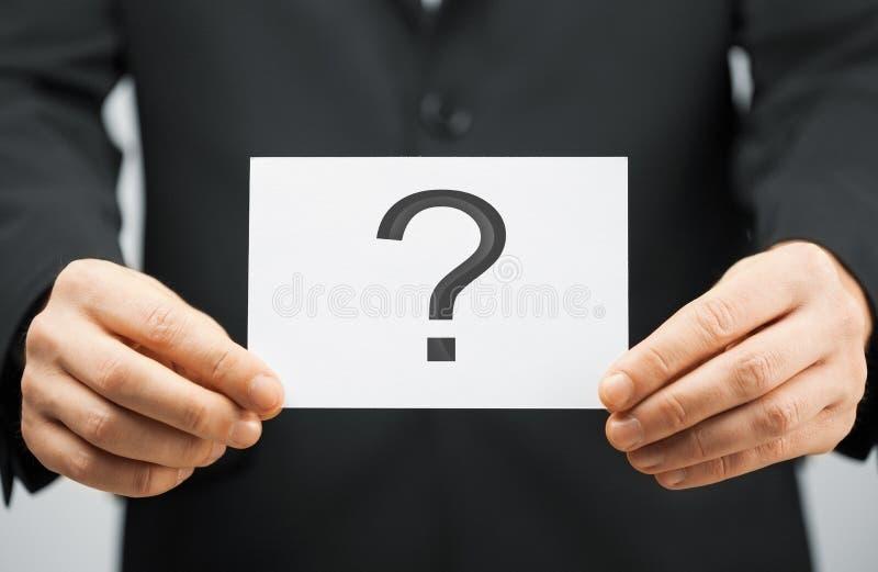 Hombre en el traje que sostiene la tarjeta con el signo de interrogación imagen de archivo