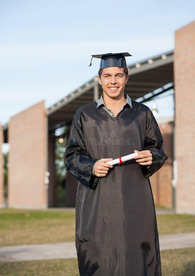 Hombre en el vestido de la graduación que sostiene el diploma en universidad fotos de archivo