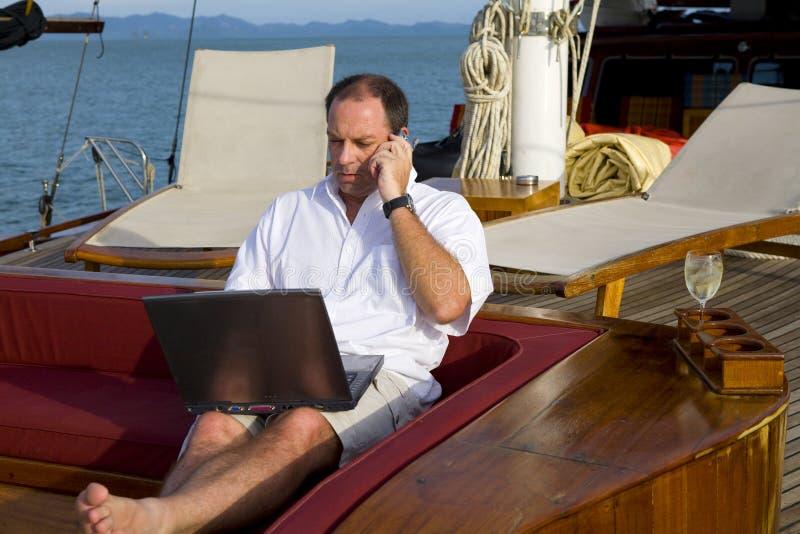 Hombre en el yate con el teléfono y la computadora portátil imagenes de archivo