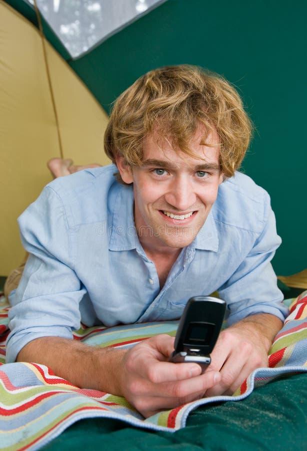 Hombre en envío de mensajes de texto de la tienda en el teléfono celular fotos de archivo libres de regalías
