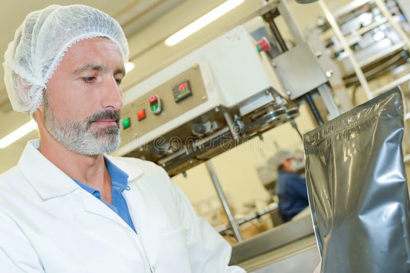 Hombre en fábrica con el bolso sellado imágenes de archivo libres de regalías
