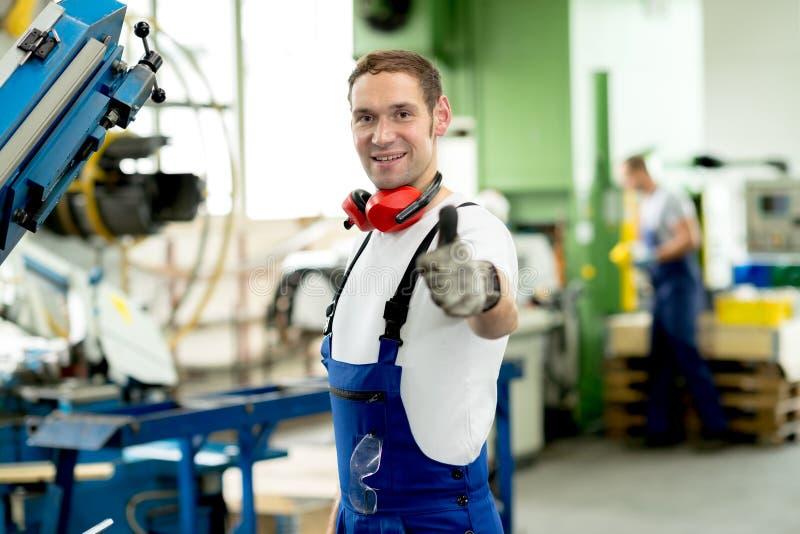 Hombre en fábrica con el pulgar para arriba foto de archivo