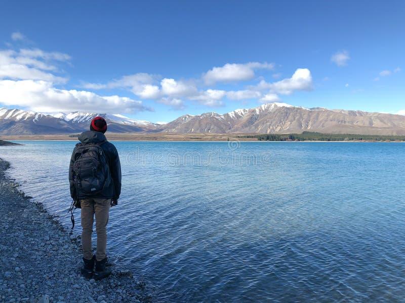 Hombre en gorrita tejida que admira la vista del lago Tekapo en Nueva Zelanda foto de archivo libre de regalías