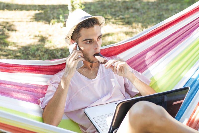 Hombre en hamaca con el teléfono imagen de archivo libre de regalías