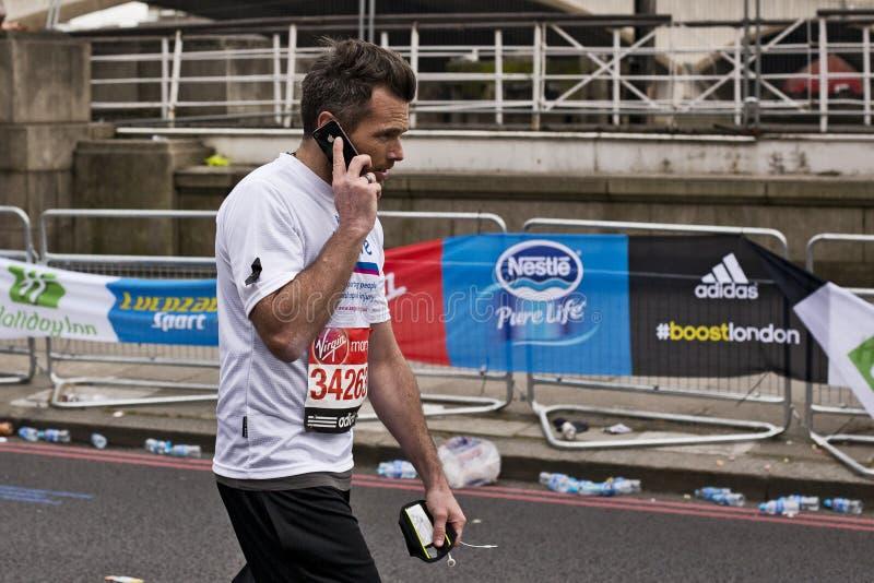 Hombre en iPhone mientras que corre el maratrhon imagen de archivo