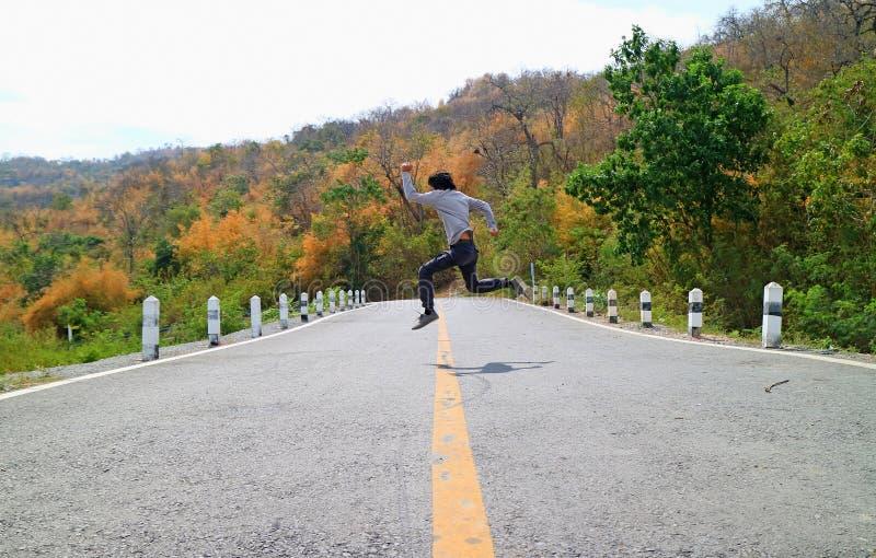 Hombre en la actitud del salto a través del camino de la montaña entre bosque cambiante del color imagen de archivo libre de regalías