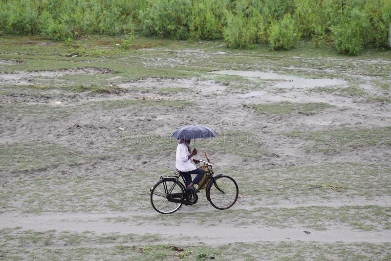 Hombre en la bici con el paraguas en la lluvia, Calcutta en la India, Asia imágenes de archivo libres de regalías