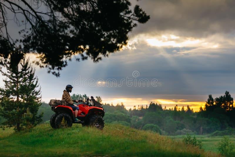 Hombre en la bici del patio de ATV que corre en la puesta del sol fotografía de archivo libre de regalías