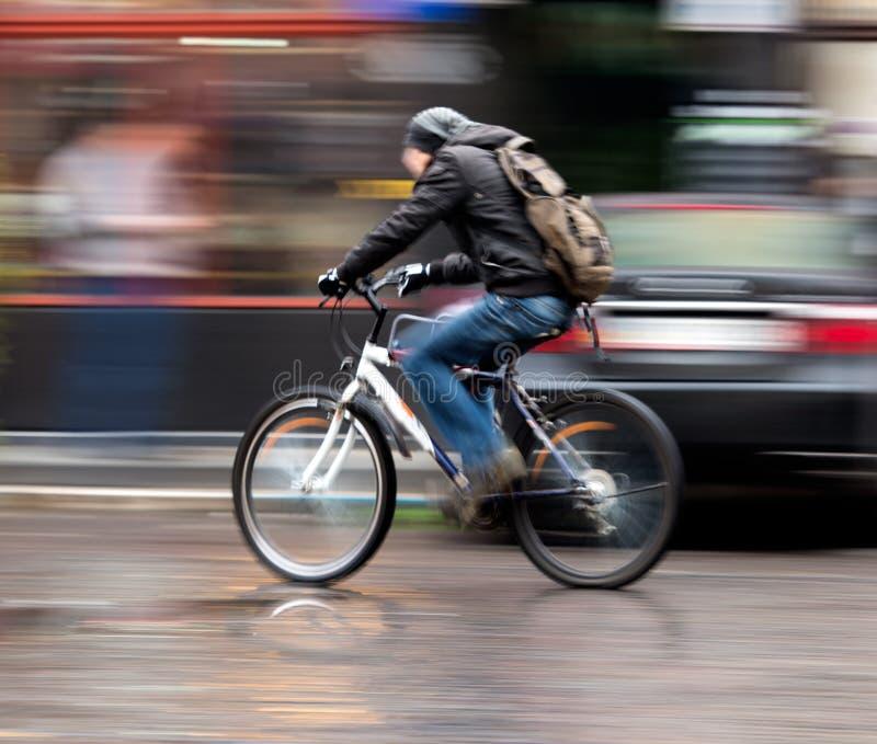 Hombre en la bicicleta en la ciudad foto de archivo