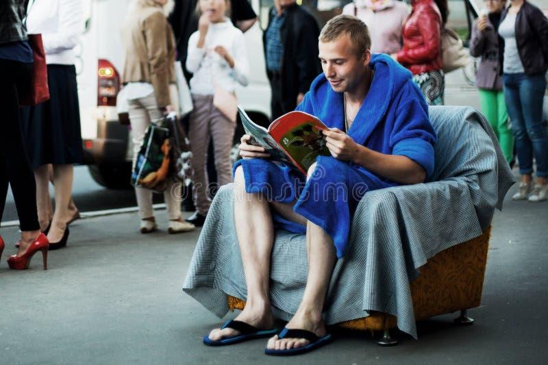 Hombre en la butaca en la ciudad foto de archivo