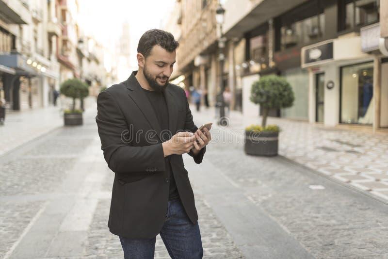 Hombre en la calle que mira smartphone imágenes de archivo libres de regalías