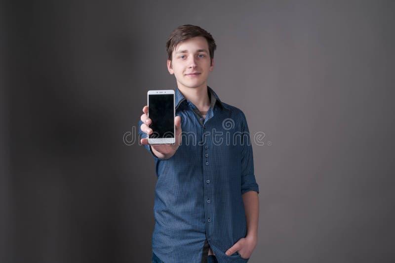 hombre en la camisa azul que mira la cámara y que muestra smartphone con la pantalla en blanco imágenes de archivo libres de regalías