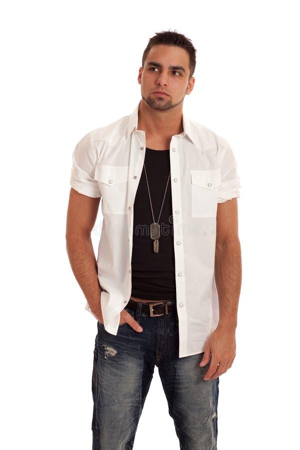 Hombre en la camisa y los pantalones vaqueros blancos foto de archivo