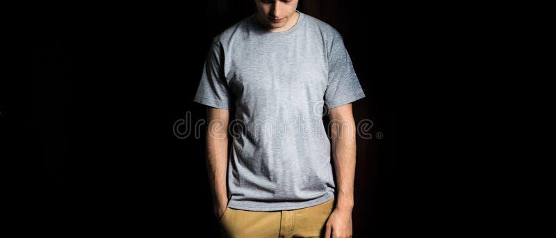 Hombre en la camiseta gris, blanca en blanco, soporte en un fondo negro, mofa para arriba fotografía de archivo