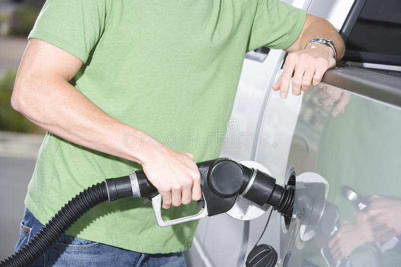 Hombre en la camiseta verde que reaprovisiona su coche de combustible foto de archivo