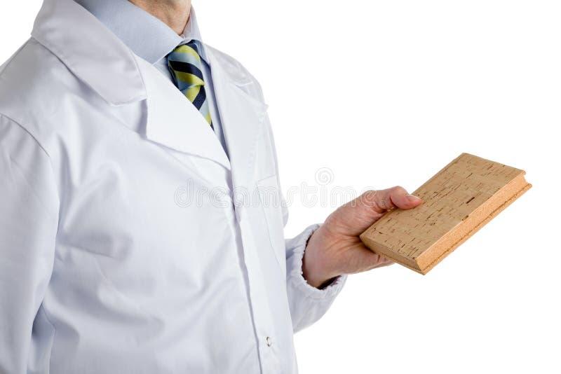 Hombre en la capa médica que sostiene el libro en blanco del corcho foto de archivo